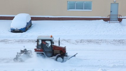 tractor cleans snow on road, moves down street in winter