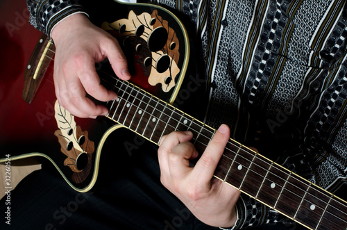 The man plays an electric guitar