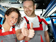 Happy apprentices in a garage are proud and show thumbs up