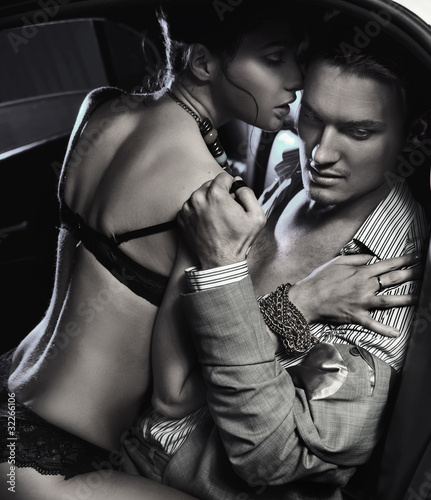 Loving couple in the car embraces in black and white