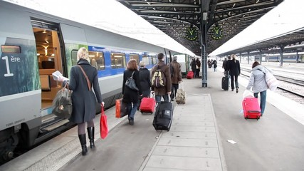 people with luggage at station are walk on platform along train