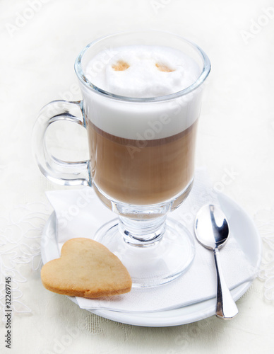 Glass of coffe with cookie on white plate