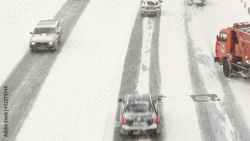traffic on the street near Moscow Kremlin under snowfall