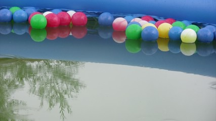 Rain drops fall in water of pool with balls. Tree reflection.