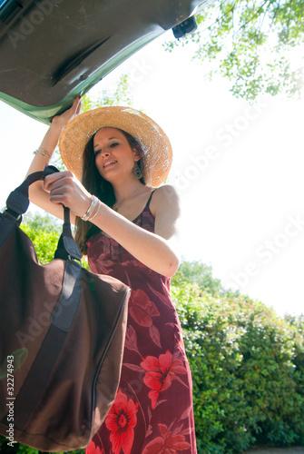 jeune femme qui met un sac dans le coffre