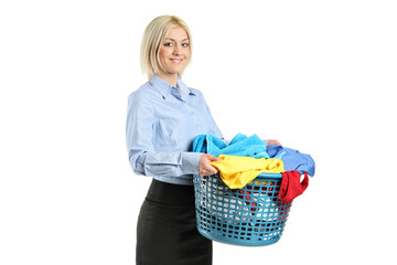 Young smiling woman holding a laundry basket