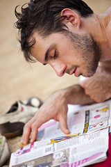 homme lit un magazine sur le sable en vacances