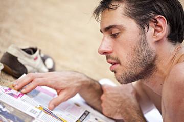 homme lit un magazine sur la plage en vacances