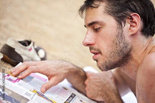 homme lit un magazine sur la plage en vacances photo libre de droits sur la banque d 39 images. Black Bedroom Furniture Sets. Home Design Ideas