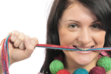 Portrait of a beautiful young girl with colored yarn in her mout