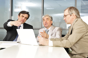 Portrait of three businessmen at the computer.