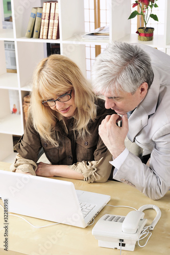 Portrait of two people working on the computer.