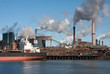 Steel factory with smokestacks and a big cargo ship