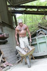 Ölverschmierter Arbeiter mit Schubkarre