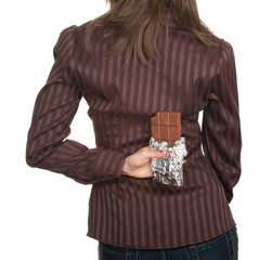 young woman holding chocolate after her back.