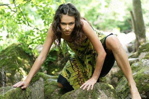 Fashion shoot of a young woman in a dress in a wild forest