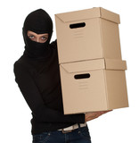 female thief in black clothes and balaclava with boxes