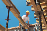 Construction worker placing formwork beams poster
