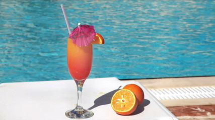Orange cocktail with umbrella and straw near swimming pool