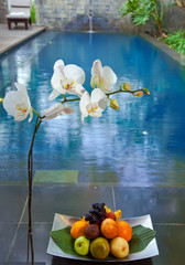 Branch orchids and a basket full fruit on background of pool..