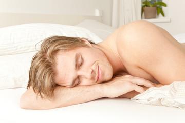 Mann liegt im Bett und ruht sich aus