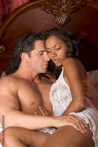 Interracial heterosexual sensual couple in bed