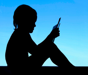 silhouette of a  reading boy