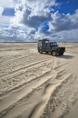 beach of St. Peter Ording with expedition four-wheel vehicle