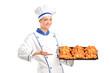 Smiling baker showing freshly baked croissants