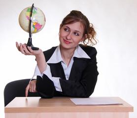 Девушка - менеджер туристического агентства с глобусом в руке