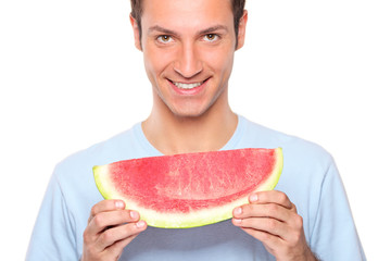 Smiling young man holding a slice of watermelon