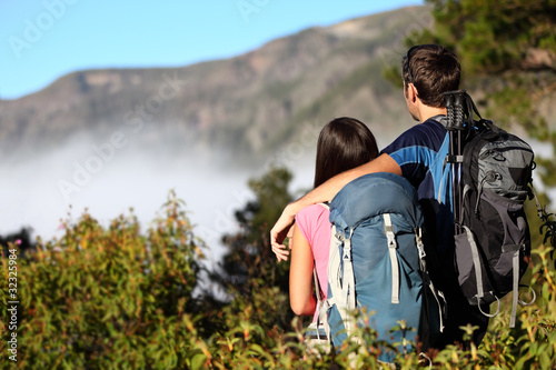 Couple hiking looking at view