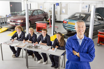 Teacher with students studying automotive trade in vocational school
