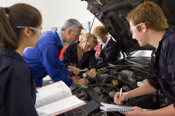 Teacher watching students repair car in automotive vocational school