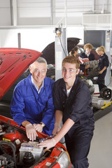 Teacher helping student repair car in automotive vocational school