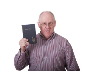 Older Man in Striped Shirt Holding Old Battered Bible
