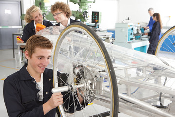 Students constructing electric vehicle prototype in vocational school