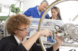 Teacher helping students constructing electric vehicle prototype in vocational school