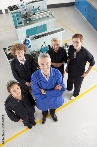 Teacher and students standing near lathes in vocational school