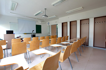 Traditional classroom with desk-chairs, chalkboard and projector