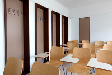 University classroom with wooden chairs and individual tables