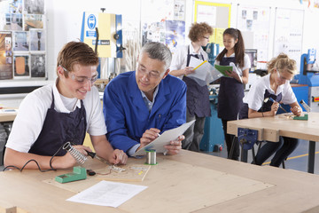 Teacher watching student using soldering iron in vocational school