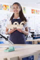 Proud student holding wooden carving in vocational school classroom