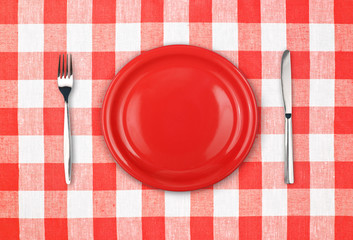 Knife, red plate and fork on checked tablecloth