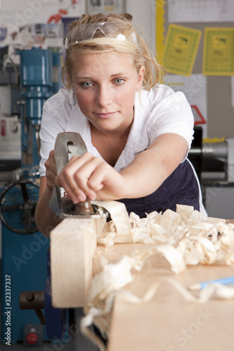 Serious student planing wood in vocational school