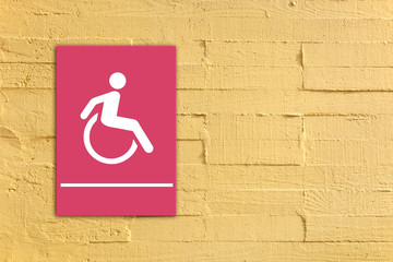Pink handicapped sign on yellow concrete wall background