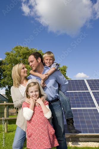 Happy family standing near large solar panels