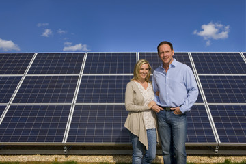 Smiling couple standing together near large solar panels