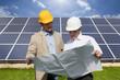 Technicians holding blueprints talking near large solar panels