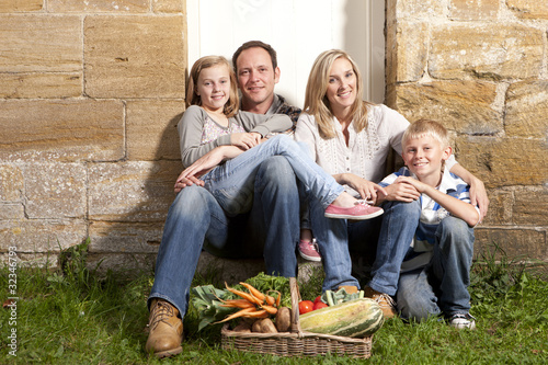 Happy family sitting together outdoors with basket full of vegetables